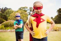 Niños que llevan el traje del super héroe que presenta para la cámara Imagenes de archivo