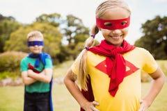 Niños que llevan el traje del super héroe que presenta para la cámara Imagen de archivo libre de regalías