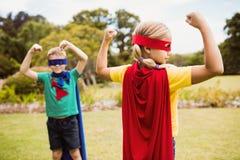 Niños que llevan el traje del super héroe que presenta para la cámara Fotografía de archivo