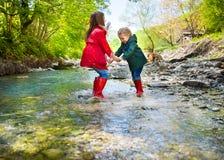 Niños que llevan las botas de lluvia que saltan en un río de la montaña foto de archivo
