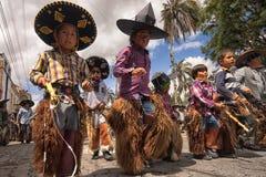 Niños que llevan los sombreros y las grietas en la calle en Ecuador Foto de archivo