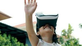 Niños que llevan los vidrios de la realidad virtual con la diversión y la situación asombrosamente de la cara al aire libre metrajes