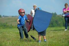 Niños que luchan con el escudo Foto de archivo