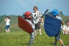 Niños que luchan con el escudo Fotografía de archivo