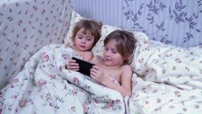 Niños que mienten debajo de la manta y del smartphone del uso almacen de metraje de vídeo