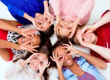 Niños que mienten en el piso comparativo con los vidrios fuera de los fingeres Fotografía de archivo