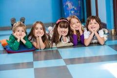 Niños que mienten en fila en piso Imagen de archivo libre de regalías