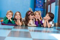 Niños que mienten en fila en piso Fotos de archivo