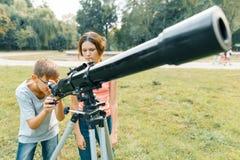 Niños que miran con interés en un telescopio al cielo foto de archivo