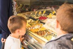 Niños que miran el helado en una tienda de helado imagen de archivo