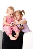 Niños que miran en el teléfono móvil Imagenes de archivo