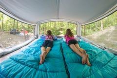 Niños que miran hacia fuera Windows del campista móvil 180 grados fotos de archivo