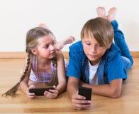 Niños que miran la pantalla de smartphones Fotos de archivo libres de regalías