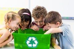 Niños que miran las botellas plásticas en el reciclaje de la caja imagenes de archivo