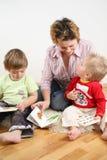 Niños que miran los libros con la madre 2 Imagen de archivo libre de regalías