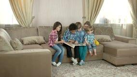 Niños que miran a través de álbum de foto almacen de metraje de vídeo