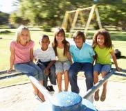 Niños que montan en cruce giratorio en patio Fotografía de archivo