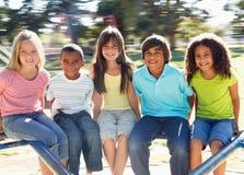 Niños que montan en cruce giratorio en patio Imágenes de archivo libres de regalías
