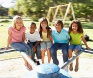 Niños que montan en cruce giratorio en patio Fotografía de archivo libre de regalías