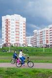 Niños que montan las bicis antes de tormenta Imágenes de archivo libres de regalías