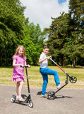 Niños que montan las vespas en un parque Imagenes de archivo