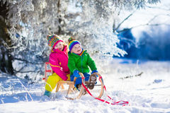 Niños que montan un trineo en parque nevoso del invierno Imagen de archivo