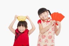 Niños que muestran el sobre y el oro rojos Foto de archivo libre de regalías