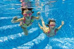 Niños que nadan bajo el agua en piscina Imágenes de archivo libres de regalías