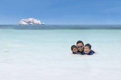 Niños que nadan con su padre en la playa Fotografía de archivo