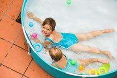 Niños que nadan en piscina del niño Imagenes de archivo