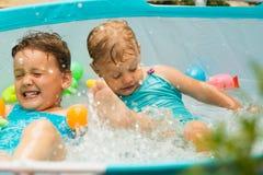 Niños que nadan en piscina del niño Imagen de archivo