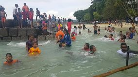 Niños que nadan en ropa por la playa en Mansinam metrajes