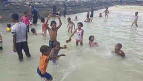 Niños que nadan en ropa por la playa en Mansinam almacen de video