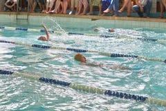 Niños que nadan estilo libre en la lección que nada foto de archivo