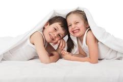 Niños que ocultan debajo de la manta Imagen de archivo libre de regalías