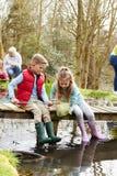 Niños que pescan en el puente en el centro de la actividad al aire libre Fotos de archivo libres de regalías