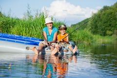 Niños que pescan en el río Foto de archivo