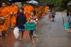 Niños que piden durante la procesión de monjes locales imagenes de archivo