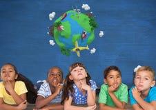 Niños que piensan junto y pared azul con el mundo de la tierra del planeta Foto de archivo libre de regalías