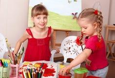 Niños que pintan en clase de arte. Imagen de archivo