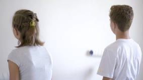 Niños que pintan la pared en sitio metrajes