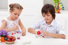 Niños que pintan los huevos de Pascua fotografía de archivo libre de regalías