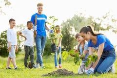 Niños que plantan árboles con los voluntarios fotos de archivo libres de regalías