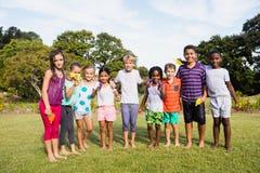 Niños que presentan junto durante un día soleado Fotos de archivo