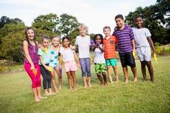 Niños que presentan junto durante un día soleado en la cámara Fotografía de archivo