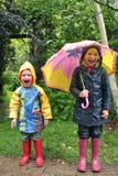 Niños que ríen con el paraguas en la lluvia imagenes de archivo
