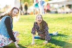 Niños que ruedan abajo la colina en hierba fotos de archivo