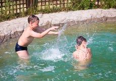 Niños que salpican en la piscina Imagen de archivo