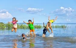 Niños que se bañan en un lago grande foto de archivo