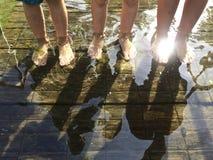 Niños que se colocan en agua con luz del sol Imagen de archivo